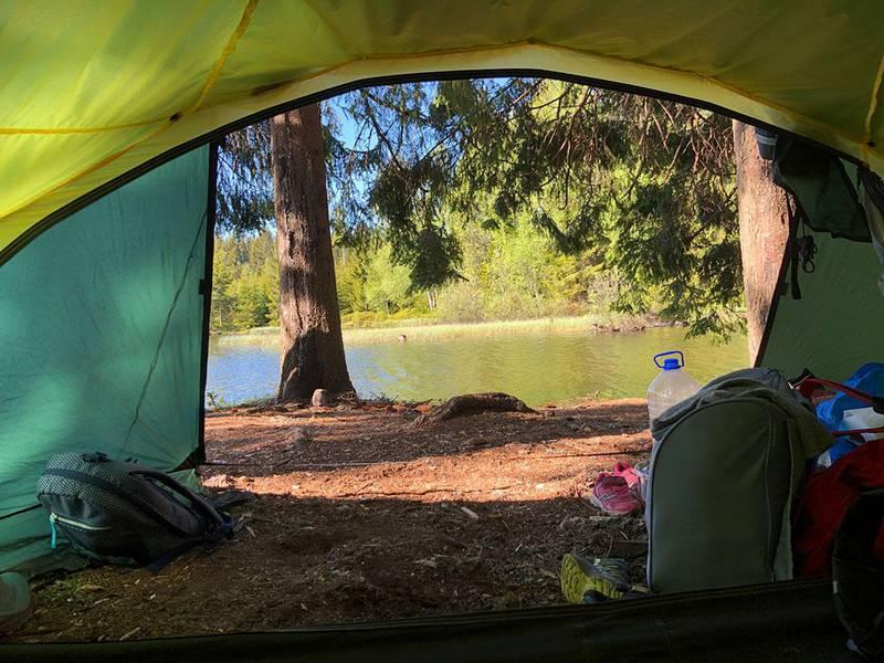Bildet viser utsikten medvann og skog fra innsiden av teltet. Dette synet kan møte deg når du våkner etter en natt i naturen.