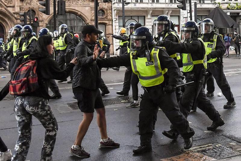 Bildet viser demonstranter som støtte sammen med politiet etter demonstrasjonen i London lørdag.
