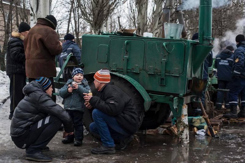 Bildet viser to voksne som gir mat til et barn i Øst-Ukraina.