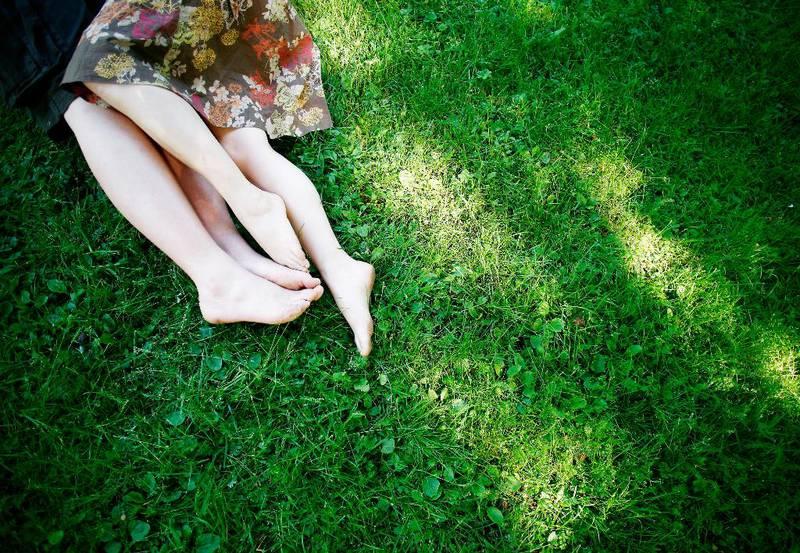 Bildet viser beina til to unge som ligger sammen i gresset.
