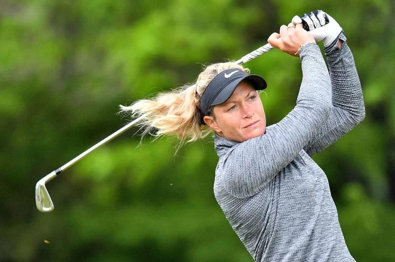 Bildet viser Suzann Pettersen rett etter et golfslag. Håret flagrer og kroppen er vridd. Over seg holder hun golf-kølla.