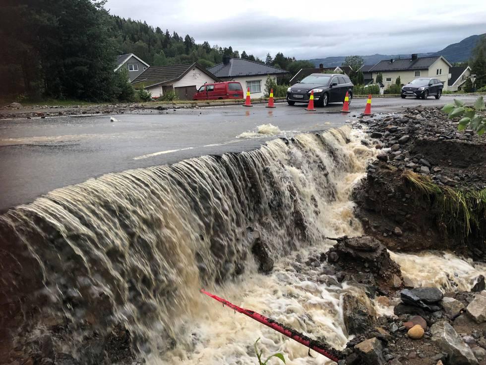 Bilet viser en oversvømt vei. Vann fosser ned fra veien og i en ødelagt grøft.