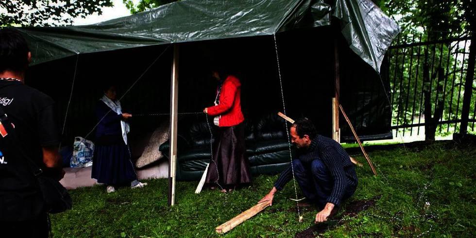 Bildet viser rumenere som har laget et telt av en presenning ved gjerdet ved Sofienberg kirke.  200 rumenske tiggere har satt opp en leir ved Sofienberg kirke i Oslo. Kirken sier de ikke kan bli boende der. Leiren blir snart et helse-problem.
