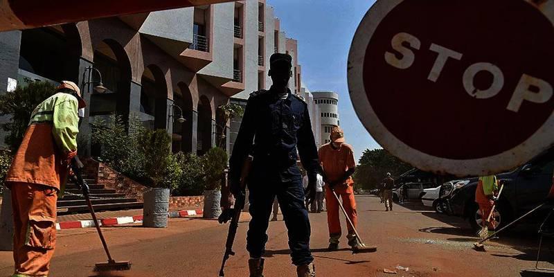 Bildet viser en politimann som holder vakt utenfor hotellet som ble utsatt for et terrorangrep fredag. Angrepet skjedde i Bamako i Mali.