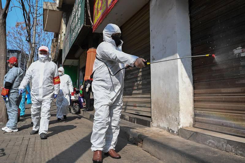 Bildet viser folk som renser stengte butikker i byen Wuhan. Over 1.000 personer har nå dødd av Wuhan-viruset i Kina.