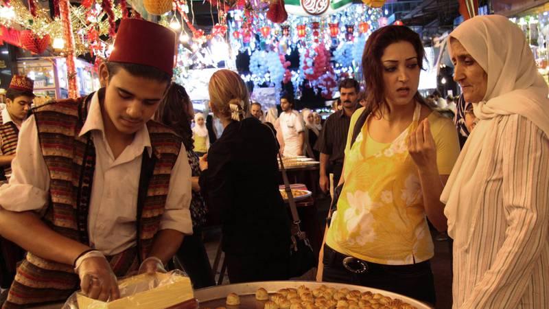 Bildet viser syriske kvinner som kjøper mat på et marked.
