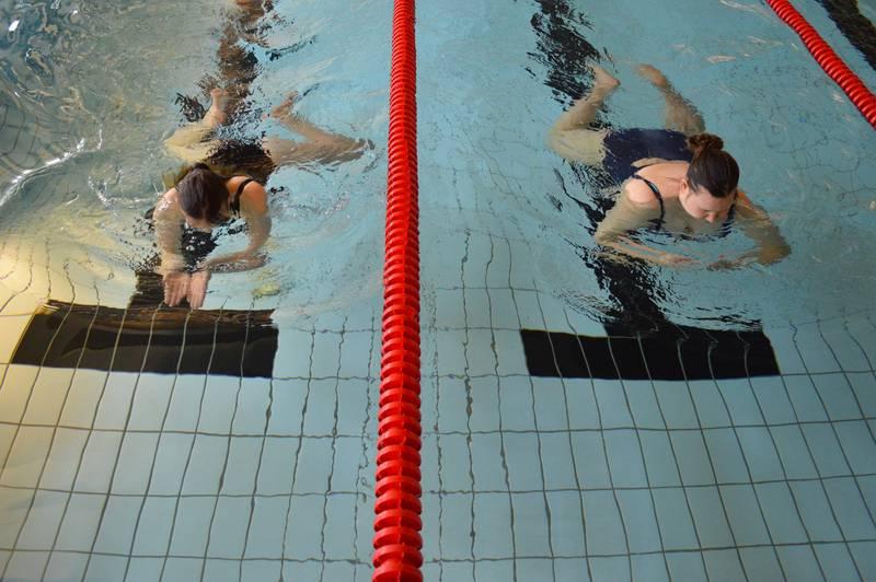 Bildet viser to jenter svømmer.