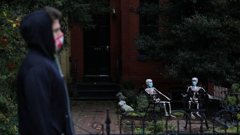 Bildet viser en mann som går fordi skjeletter med munnbind. Bildet er fra USA.