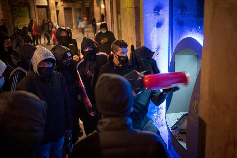 Demonstrators use an extinguisher to destroy a cash machine during a protest condemning the arrest of rap singer Pablo Hasél in Barcelona, Spain, Friday, Feb. 19, 2021. Violent street protests over the imprisonment of a rapper have erupted for a fourth straight night in Spain. Police in the northeastern region of Catalonia said some protesters pelted officers with bottles, stones, fireworks and paint on Friday. (AP Photo/Emilio Morenatti)