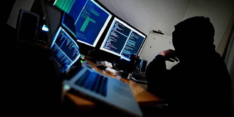 Bildet viser en person som driver med datahacking foran flere dataskjermer.