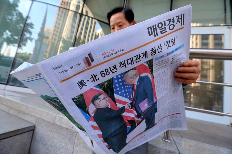 Bildet viser en mann som leser en avis i Sør-Koreas hovedstas Seoul. På forsiden er det bilde og sak fra møtet mellom Donald Trump og Kim Jong-un.