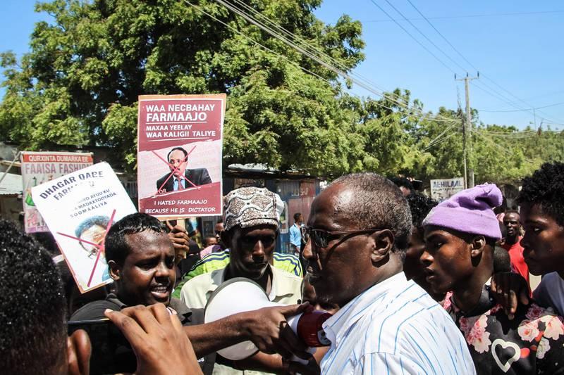 Bildet er av folk i Somalia som protesterer. De viser at de er misfornøyd med presidenten i landet. De holder opp plakater med bilder av ham, hvor de har tegnet et kryss over.
