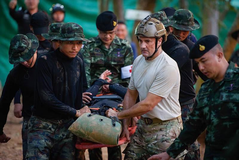 Bildet viser redningsmenn som frakter en av guttene ut av grotten i en scene fra filmen.