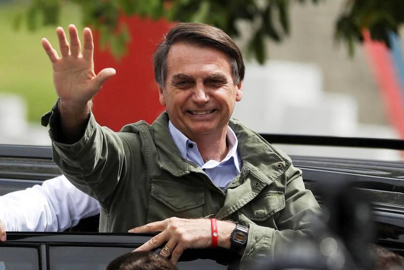 Bildet viser president  Jair Bolsonaro som vinker fra en bil.