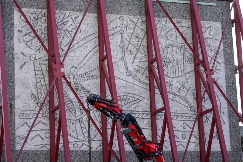 Bildet er av kunstverket «Fiskerne». Det er en rød stålramme rundt kunsten. Slik skal det kunne fraktes trygt.