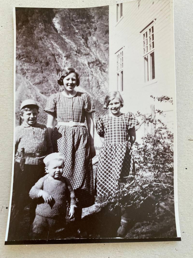 Bildet viser fire barn foran et hus.