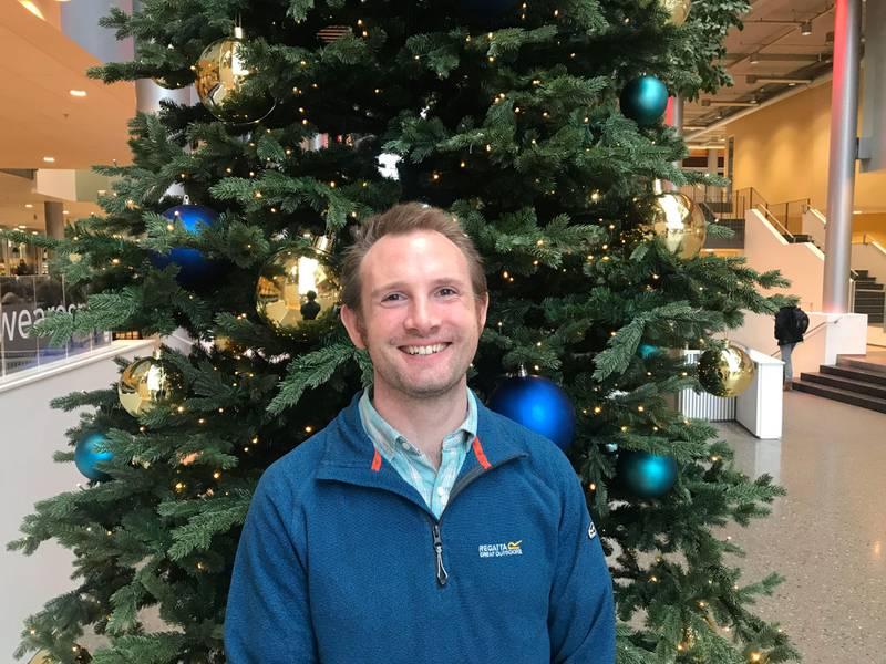 Bildet viser Craig Aaen Stockdale som står foran et juletre. I Storbritannia dømmer folk om hvit jul. Det får de sjelden, forteller han.