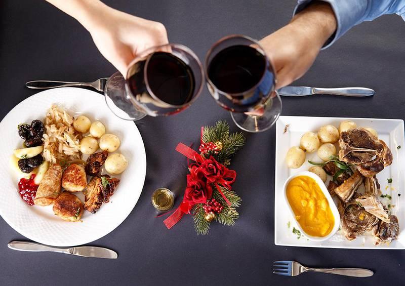 Bildet viser en tallerken med ribbe og en med pinnekjøtt. To hender skåler i rødvin. De fleste spiser den samme maten på julaften hvert år.