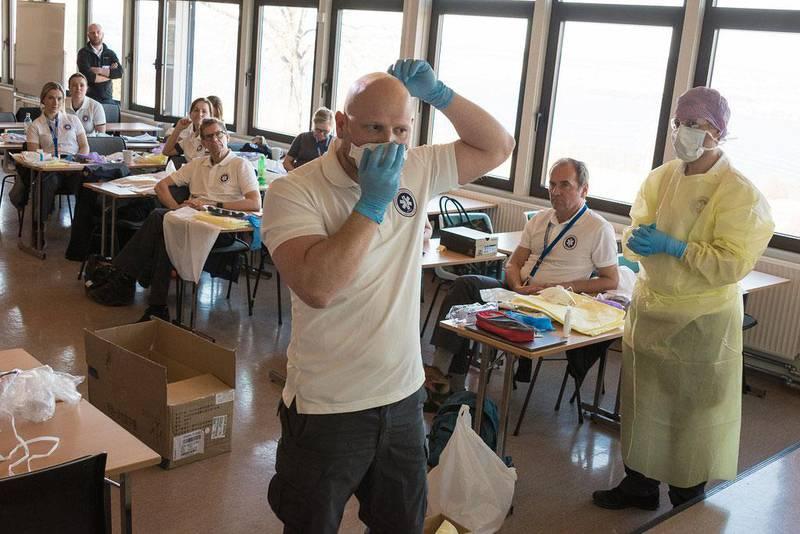 Bildet viser de norske legene og sykepleierne før avreise. De får opplæring i å bruke smittevern-utstyr.