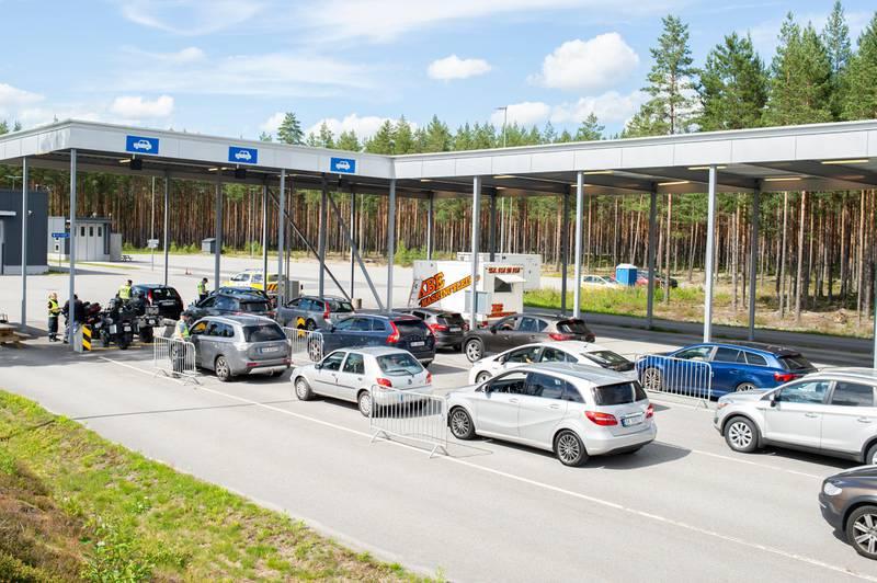 Bildet er av biler i kø. De venter på å få vise fram passet, slik at de får komme tilbake til Norge.