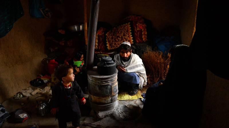 Bildet viser en familie som varmer seg inne i et telt. De fryser.
