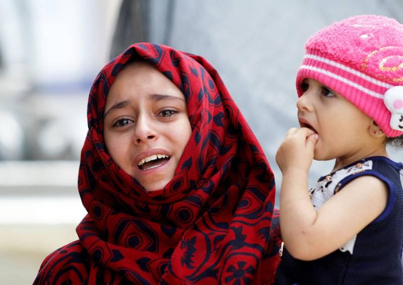Bildet viser en jente som gråter mens hun bærer på lillesøsteren sin.