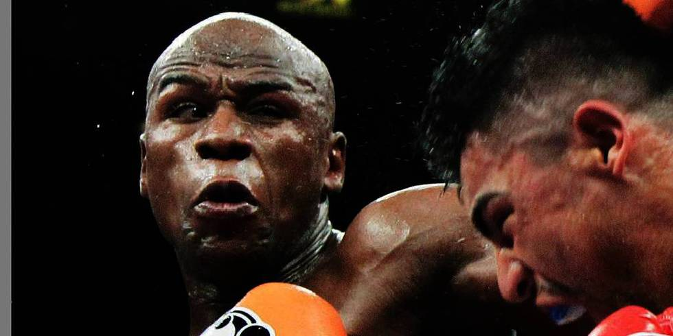 Bildet viser to menn i boksekamp. Mannen til venstre er Floyd Mayweather.