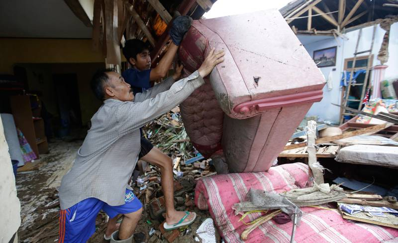 Bildet viser folk som løfter en ødelagt sofa.