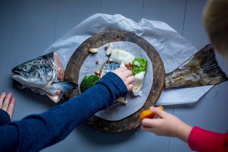 Bildet viser barnehender som strekker seg mot en tallerken med fiskemiddag.
