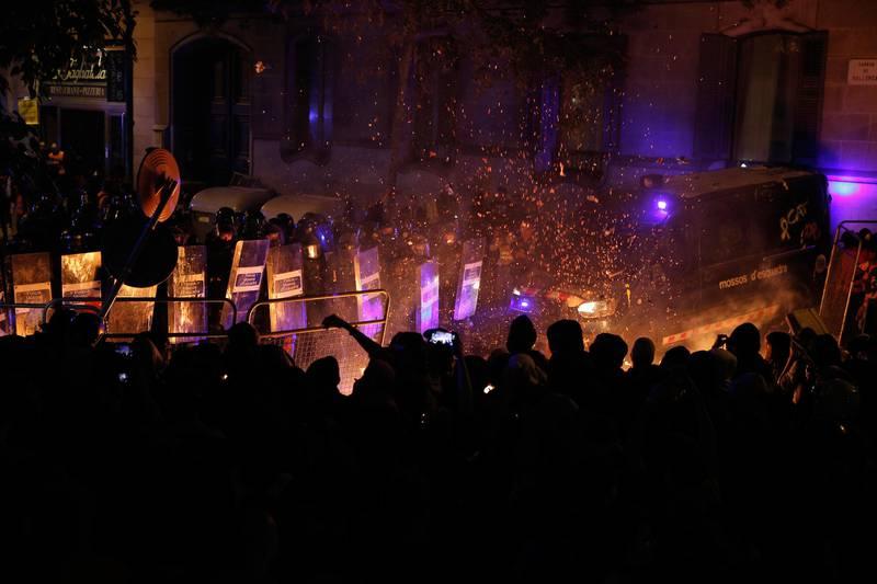 Bildet viser en gruppe demonstranter og politi bak skjold. 97 personer har blitt pågrepet siden demonstrasjonene startet denne uka. Bildet er fra tirsdag.