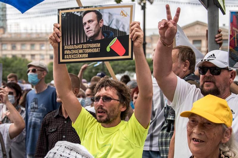 Bildet viser en demonstrant som holder opp et bilde av Aleksej Navalnyj.