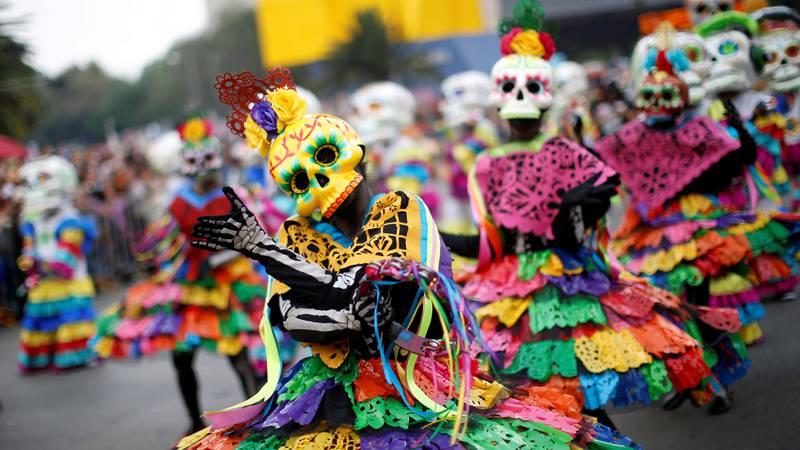 Bildet viser folk i kostymer i en parade i anledning De dødes dag i Mexico.