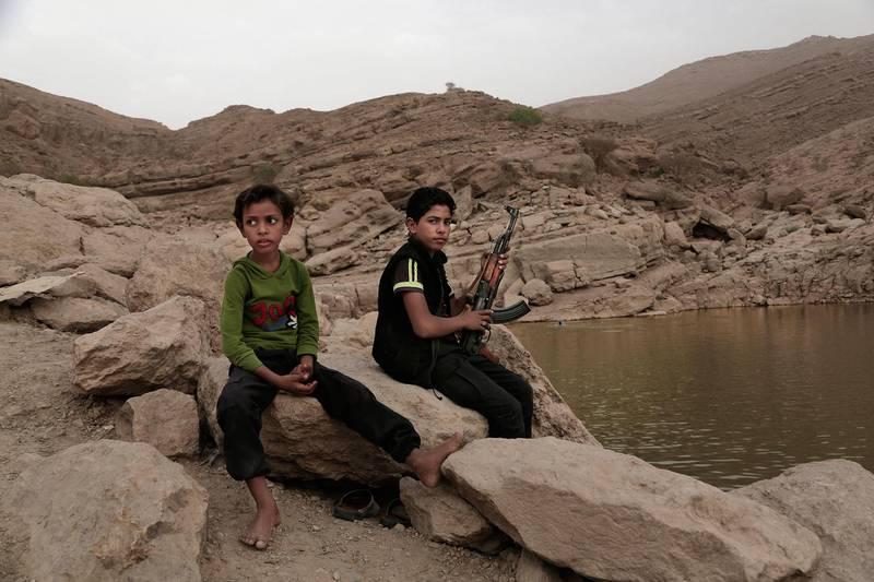 Bildet viser to barn i Jemen. Den ene er en 17 år gammel barnesoldat. Han holder et våpen. 18.000 barn skal være tvunget til å krige for opprørerne i Jemen.