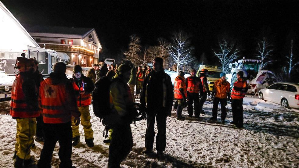 Bildet viser redningsfolk som er samlet på et tun i Troms. De skal lete etter savnede turgåere.