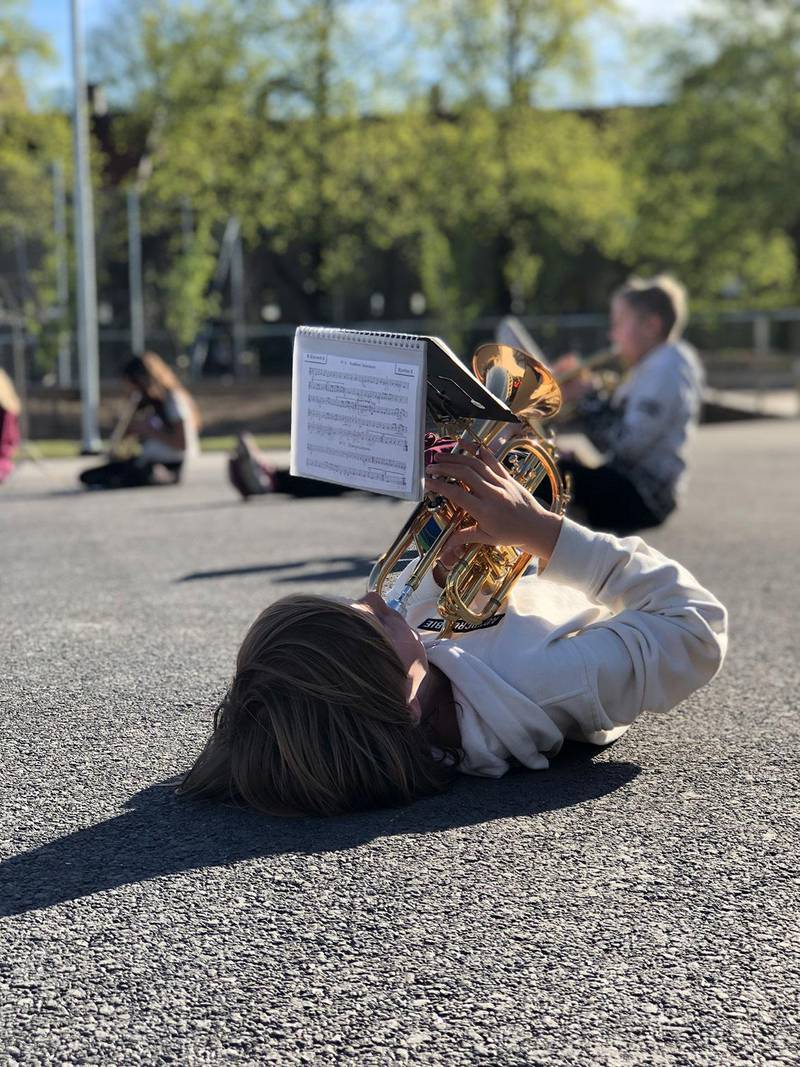 Bildet viser Amund Sandberg Fætten som ligger på bakken mens han øver på en marsj til 17. mai. Under deler av øvelsen får barna spille i den stillingen de vil.