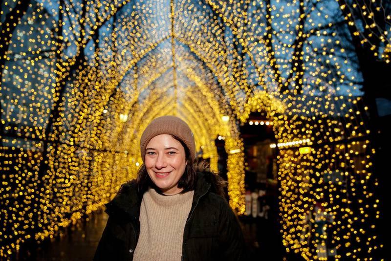 Bildet viser forfatteren Jenny Gladwell med julelys i Oslo sentrum i bakgrunnen. Gladwell har skrevet boka «Adventsgaven». Den handler om julegrana som Oslo gir i gave til London hvert år.