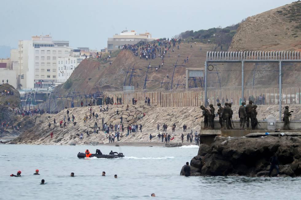 Bildet er av folk som svømmer og padler i gummibåter rundt en molo. Det er et høyt gjerde, og grensevakter langs gjerdet. Det er grensa mellom Marokko, og en spansk by i Nord-Afrika. Personene i vannet er migranter.