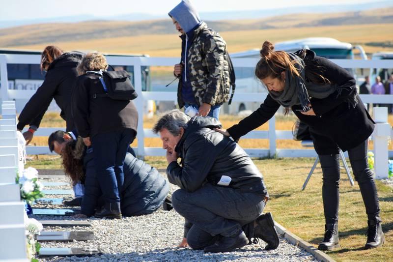 Bildet viser folk som sørger ved graver.