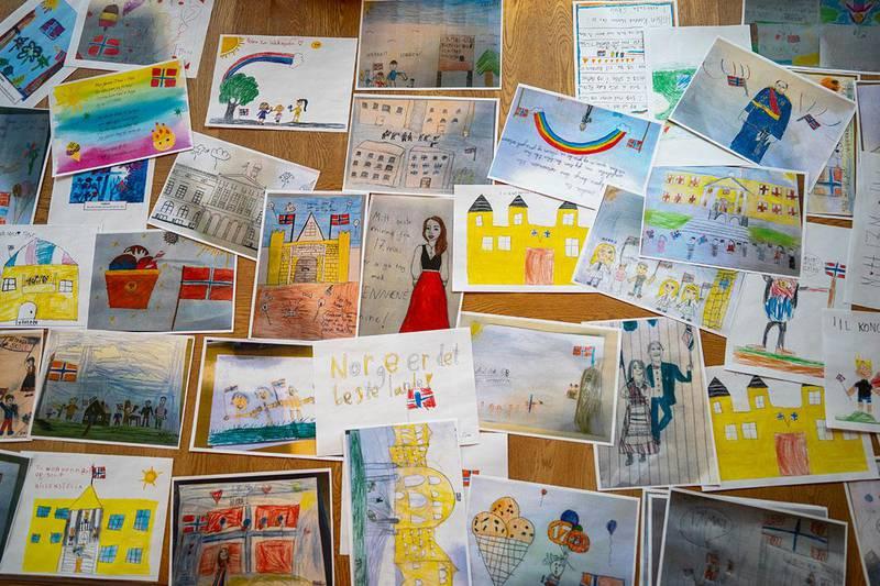 Bildet viser mange tegninger. Barn har tegnet det de forbinder med 17. mai. Kongeparet skal få alle tegningene på 17. mai.