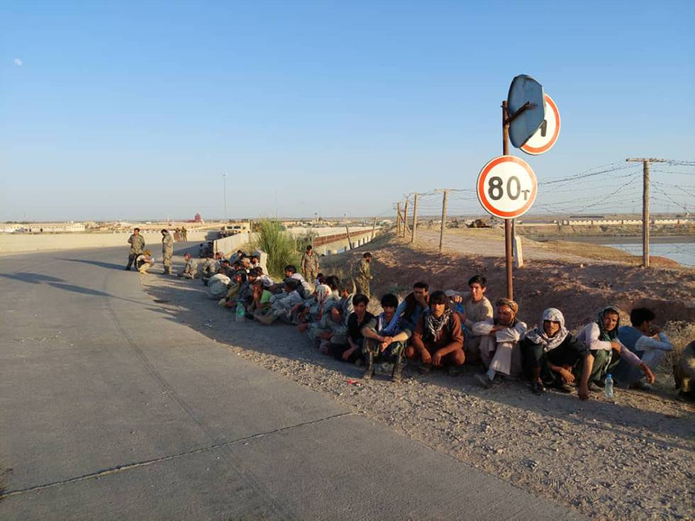 Bildet er av folk som har søkt tilflukt i Tadsjikistan. Flere av dem er soldater fra regjeringshæren i Afghanistan. De sitter i veien ved grensa. Det er en bro i bakgrunnen. Foto: Grensevakten i Tadsjikistan / AP / NTB