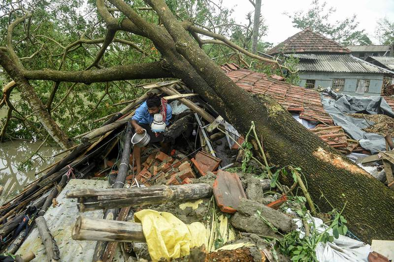 A man salvages items from his house damaged by cyclone Amphan in Midnapore, West Bengal, on May 21, 2020. - At least 22 people died as the fiercest cyclone to hit parts of Bangladesh and eastern India this century sent trees flying and flattened houses, with millions crammed into shelters despite the risk of coronavirus. (Photo by Dibyangshu SARKAR / AFP)