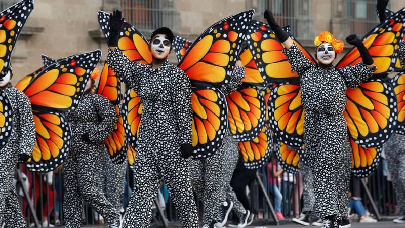 Bildet viser folk i sommerfugl-kostymer i Mexico by.