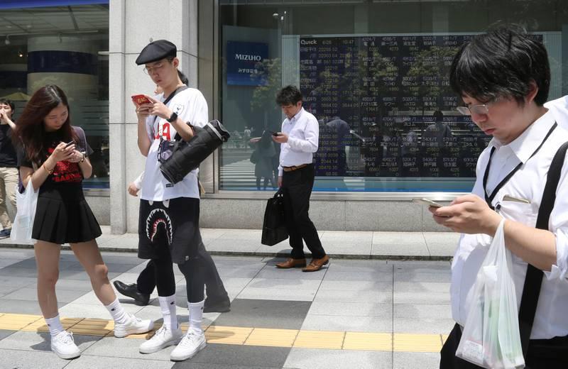 Bildet viser japanere med mobiltelefoner på gata i Tokyo.