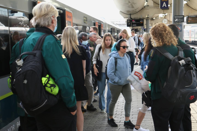 Bildet viser folk som går ut og inn av toget