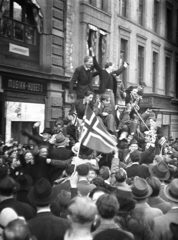 Oslo 19450508:  Fredsdagene mai 1945. Frigjøringsdagen 8. mai, jubel på Karl Johans gate. Biler fulle av jublende mennesker med norske flagg, folkemengder i gatene.Foto: Kihle / NTB / Scanpix