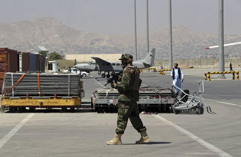 En Taliban-soldat holder vakt på rullebanen på flyplassen i Kabul. Foto: Wali Sabawoon / AP / NTB