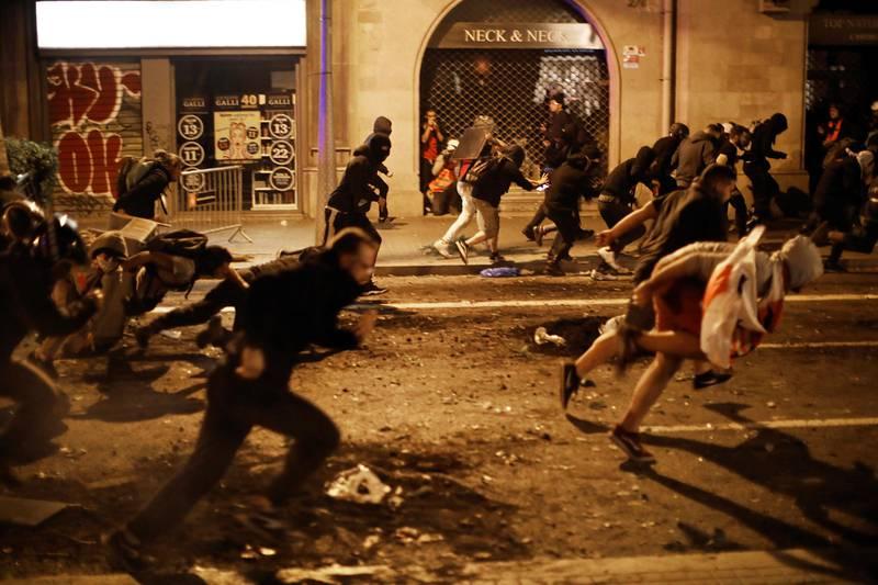Bildet viser demonstranter som løper bortover en gate. Det er ventet enda større demonstrasjoner i Barcelona fredag kveld.