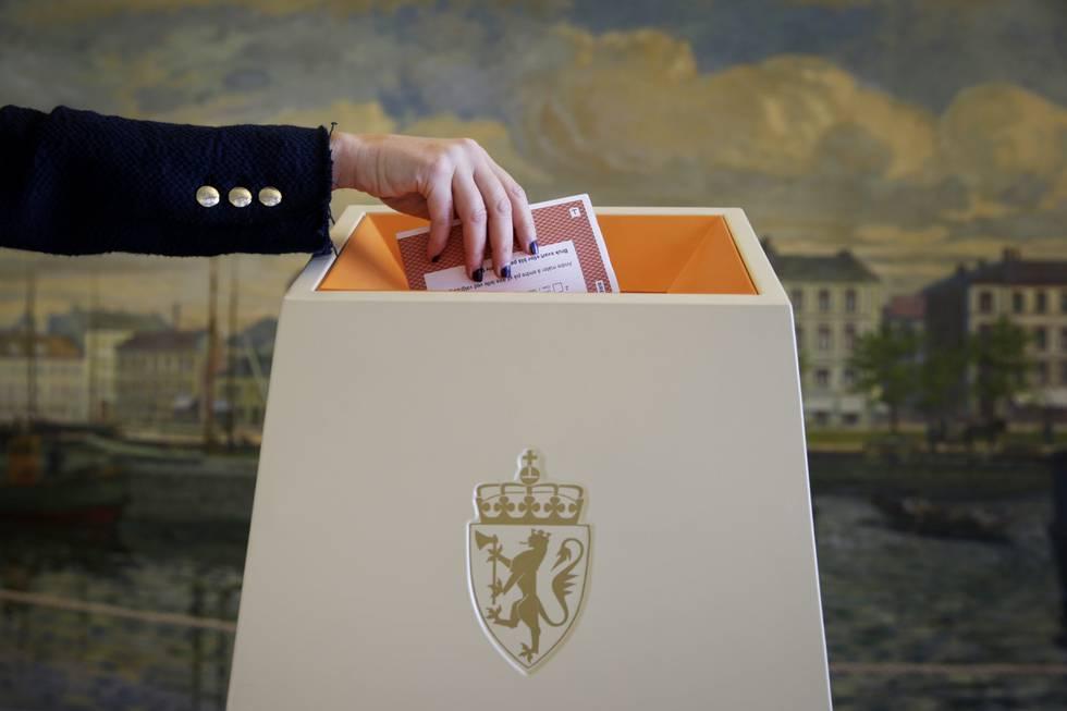 Bildet er av en arm som putter en stemmeseddel i en valgurne. I bakgrunnen er det en vegg med et påmalt bylandsskap. Foto: Håkon Mosvold Larsen / NTB / NPK
