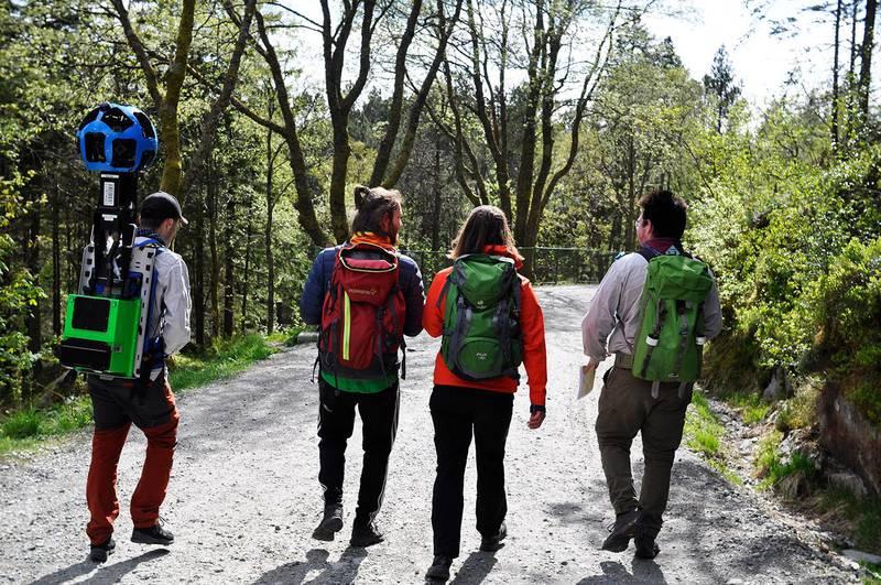 Bildet viser fire speidere som går på en vei i skogen. Den ene av dem bærer kameraet på ryggen.
