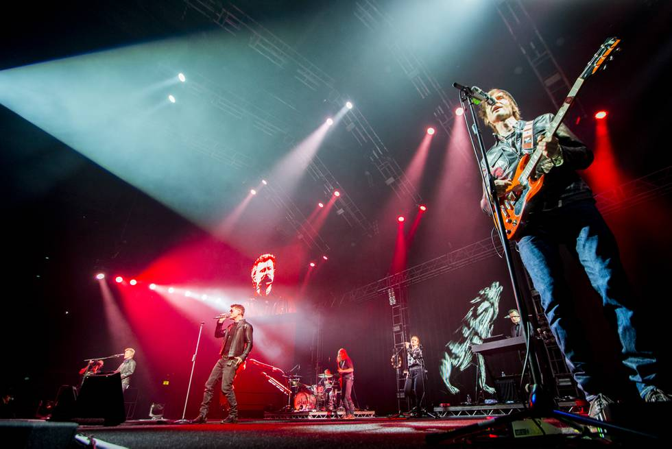 Bildet er av bandet a-ha som står på en scene i Oslo spektrum. De er omgitt av rødt og hvitt lys mens de spiller og synger. Foto: Vegard Wivestad Grøtt / NTB